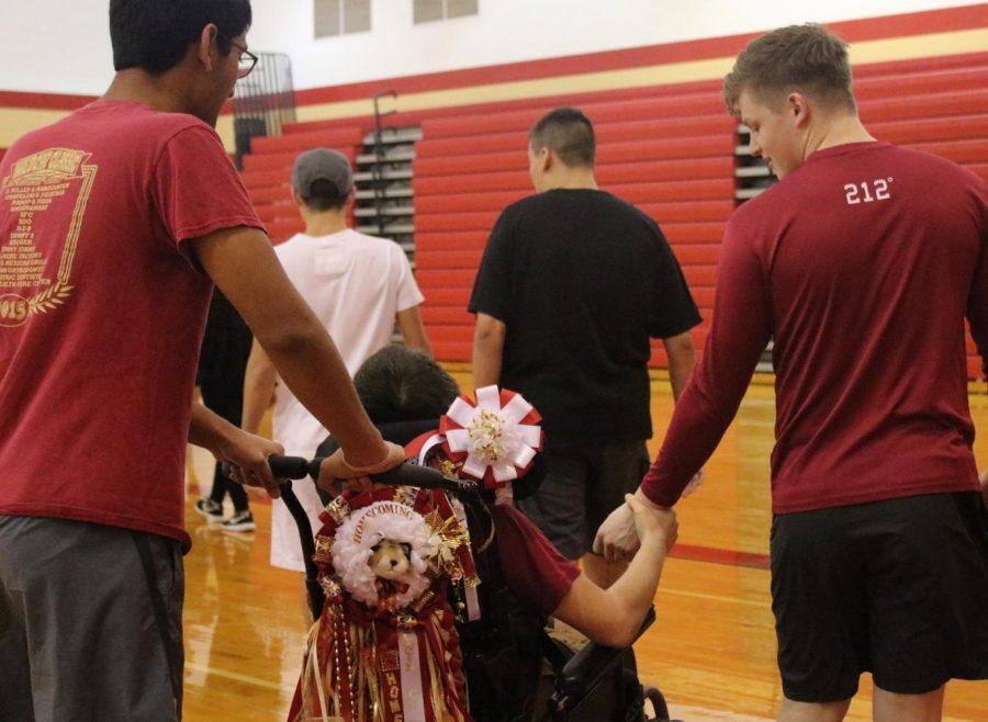 Senior Chakra Jonnalagadda pushes sophomore  Austin Matheson while he holds senior Peyton Dunman's hand.