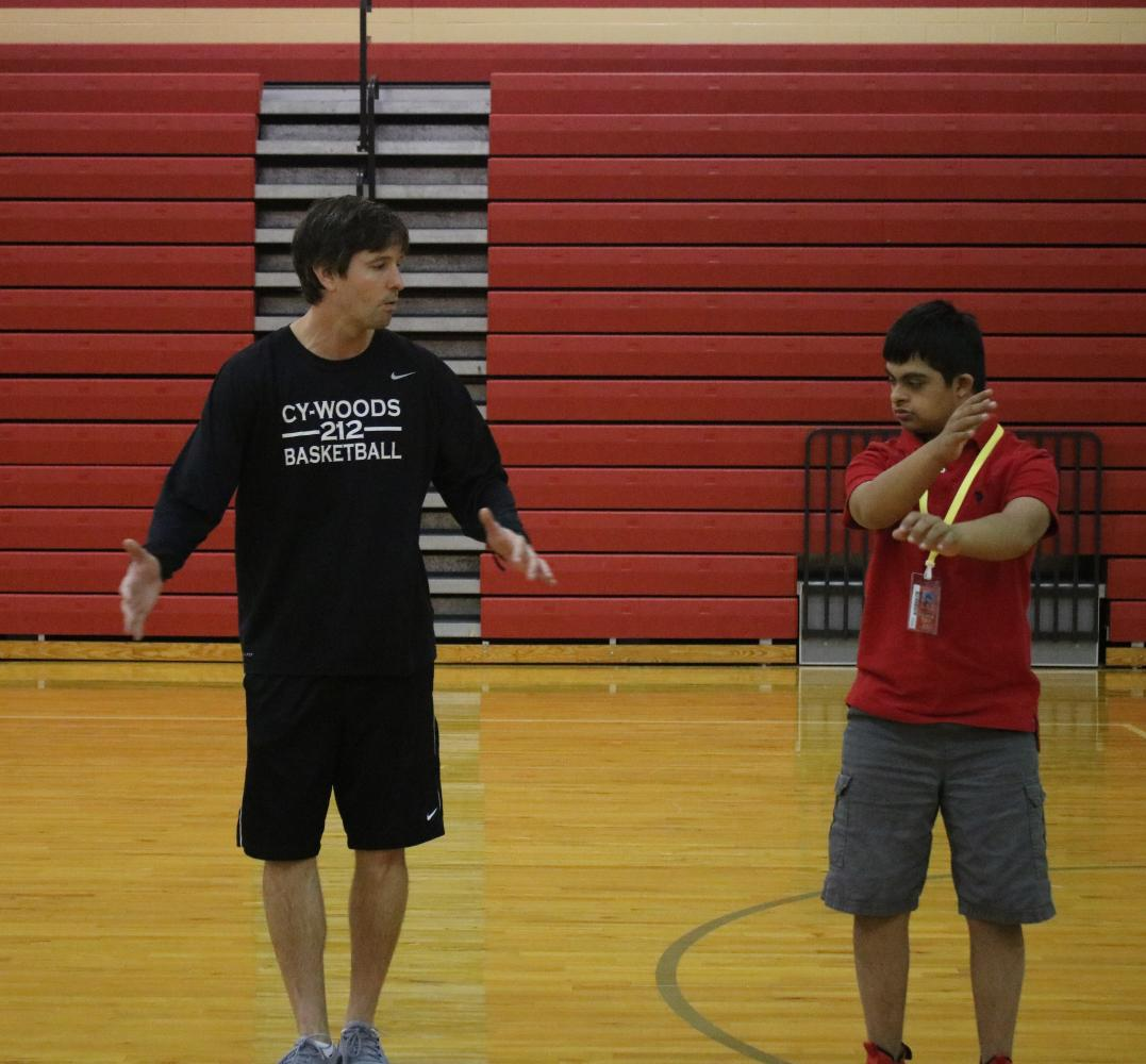 Freshman+Rishi+Trivedi+helps+Coach+Voelkel+lead+the+class+with+daily+exercises.+