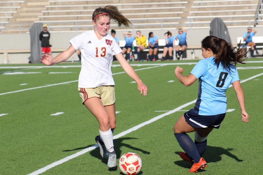 Sophomore Taylor Sims tries to keep control of the ball from a Lamar player during the game against Lamar High School.