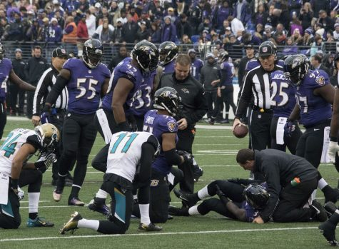 An NFL player from an injury and fellow players gather around.