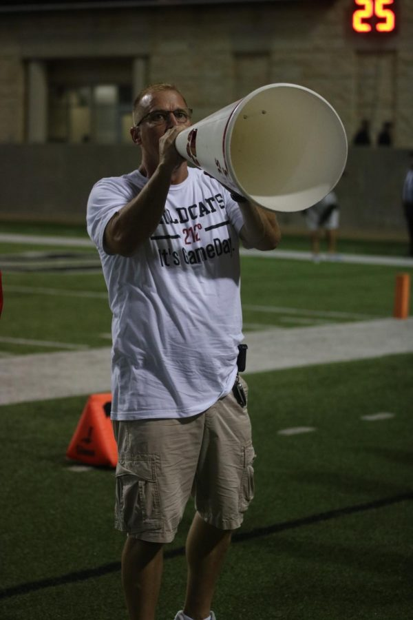 Associate Principal Dirk Heath rallies the crowd with the use of a megaphone at varsity football game against Cy-Ridge on September 27