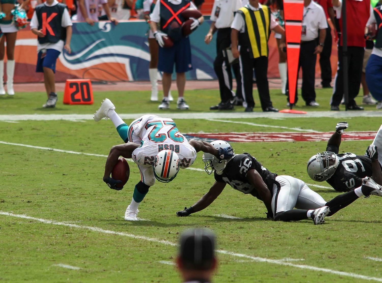 Oakland Raiders' defender tackles Miami Dolphins' running back Reggie Bush on September 16, 2012