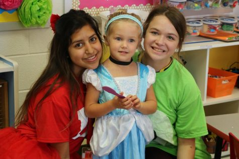 Student teachers, Desiree Diaz and Madison Webb interact with preschooler, Eliza, on Disney Character Day.