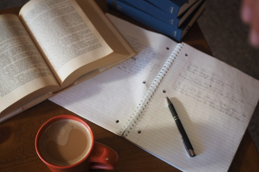 Coffee and books being used to make studying comfortable.