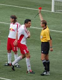 Thomas Linke of Red Bull Salzburg is shown a red card after committing a foul.